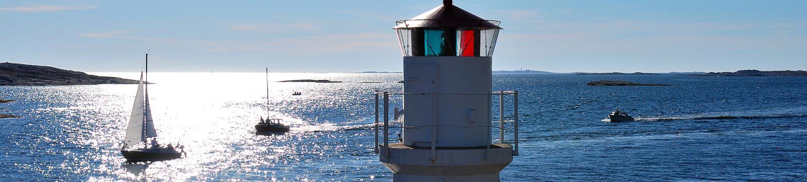 Fyr i förgrunden, hav, kobbar och segelbåt i bakgrunden